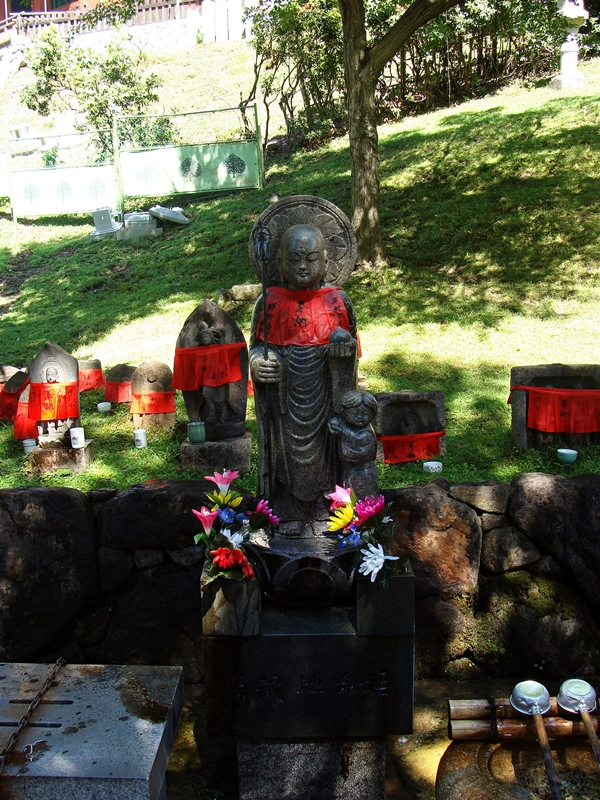 Buddha Statue mit Blumen und einem roten Latz